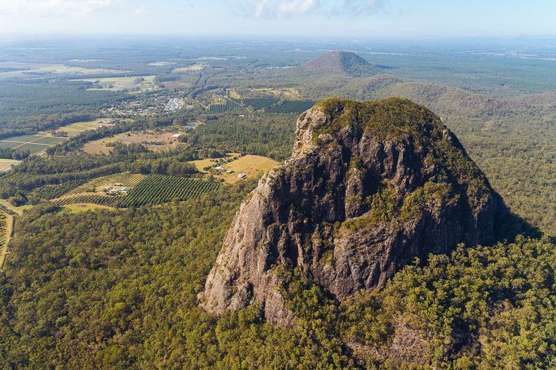 North Eastern view of Mt Tibrogargan in the foreground, with the the little guy Mt Cooee behind. Caloundra is off in the distance behind.